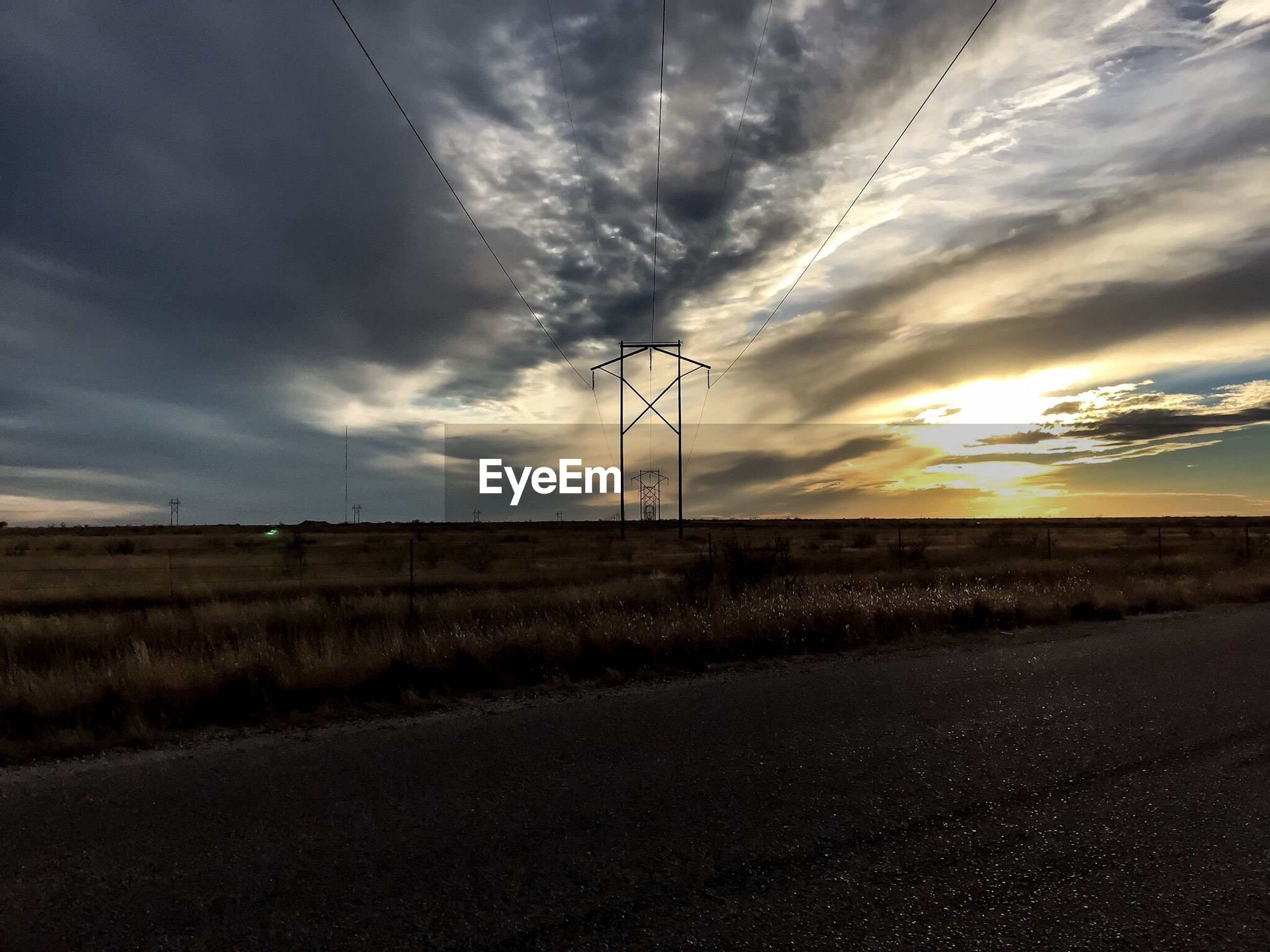 Electricity pylon of grassy field against cloudy sky during sunset