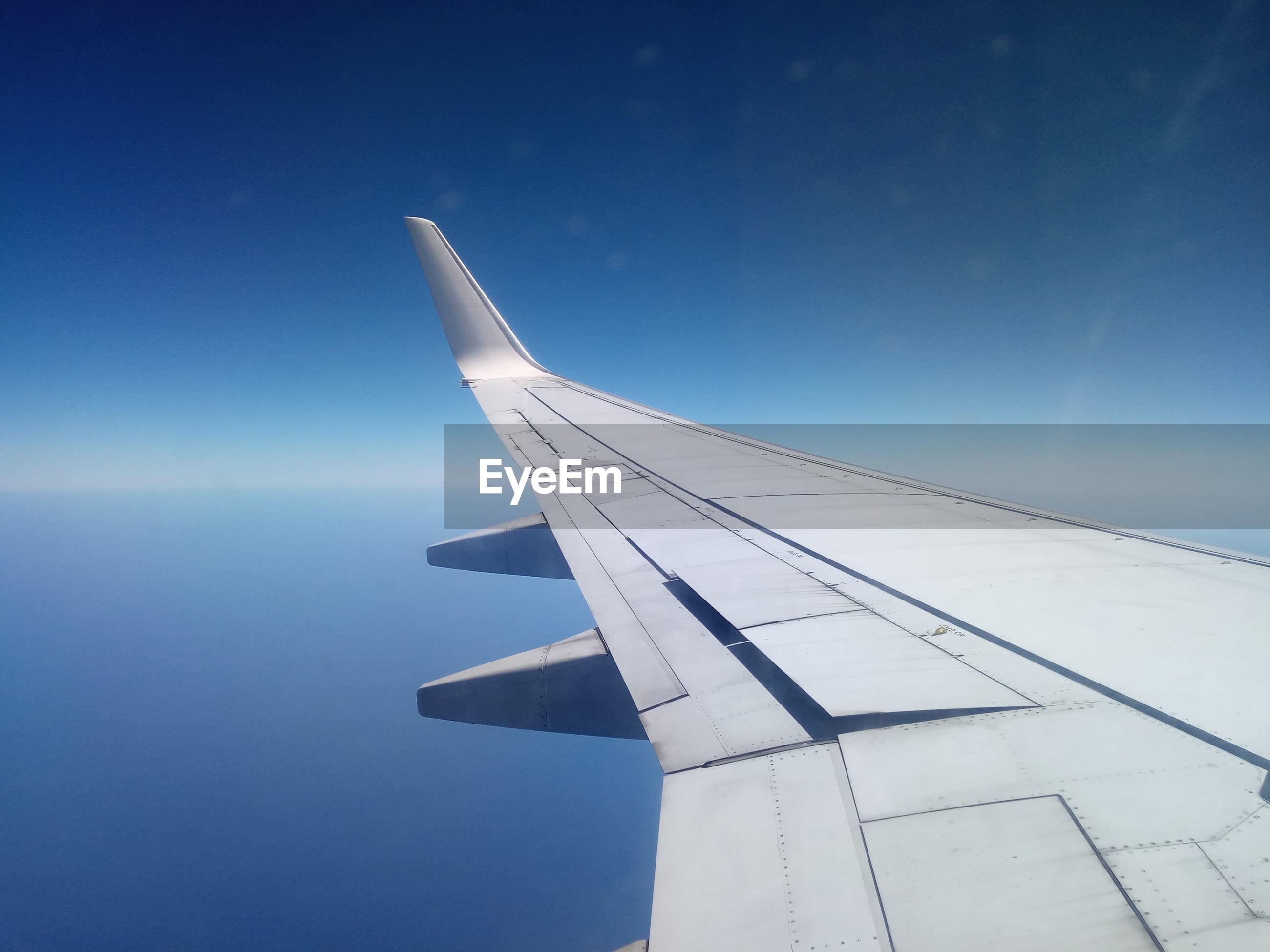 Airplane wings flying in blue sky