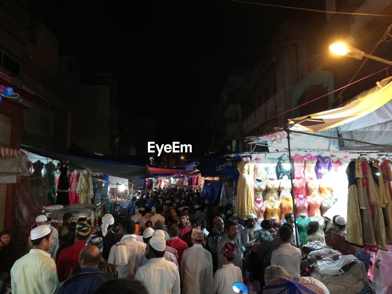 illuminated, market, crowd, retail, real people, market stall, night, city, large group of people, street, architecture, group of people, built structure, women, shopping, building exterior, adult, choice, men, store, street market, consumerism, light, bazaar, busy