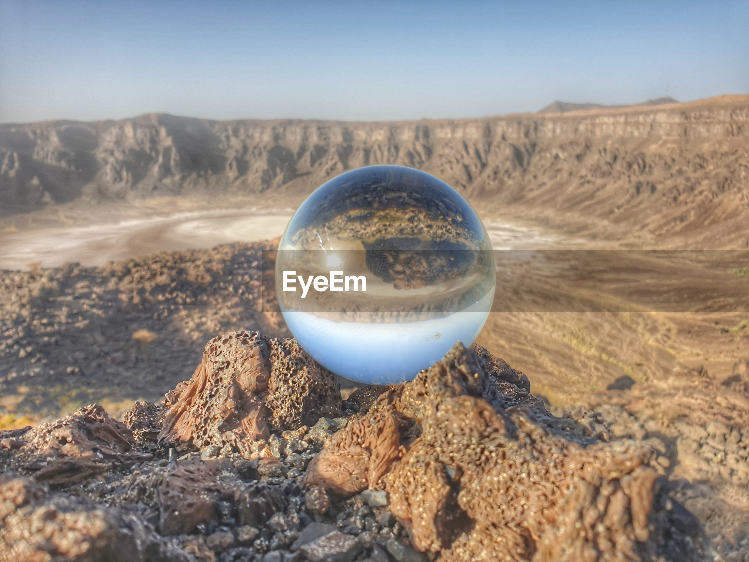 CLOSE-UP OF CRYSTAL BALL ON ROCK IN DESERT