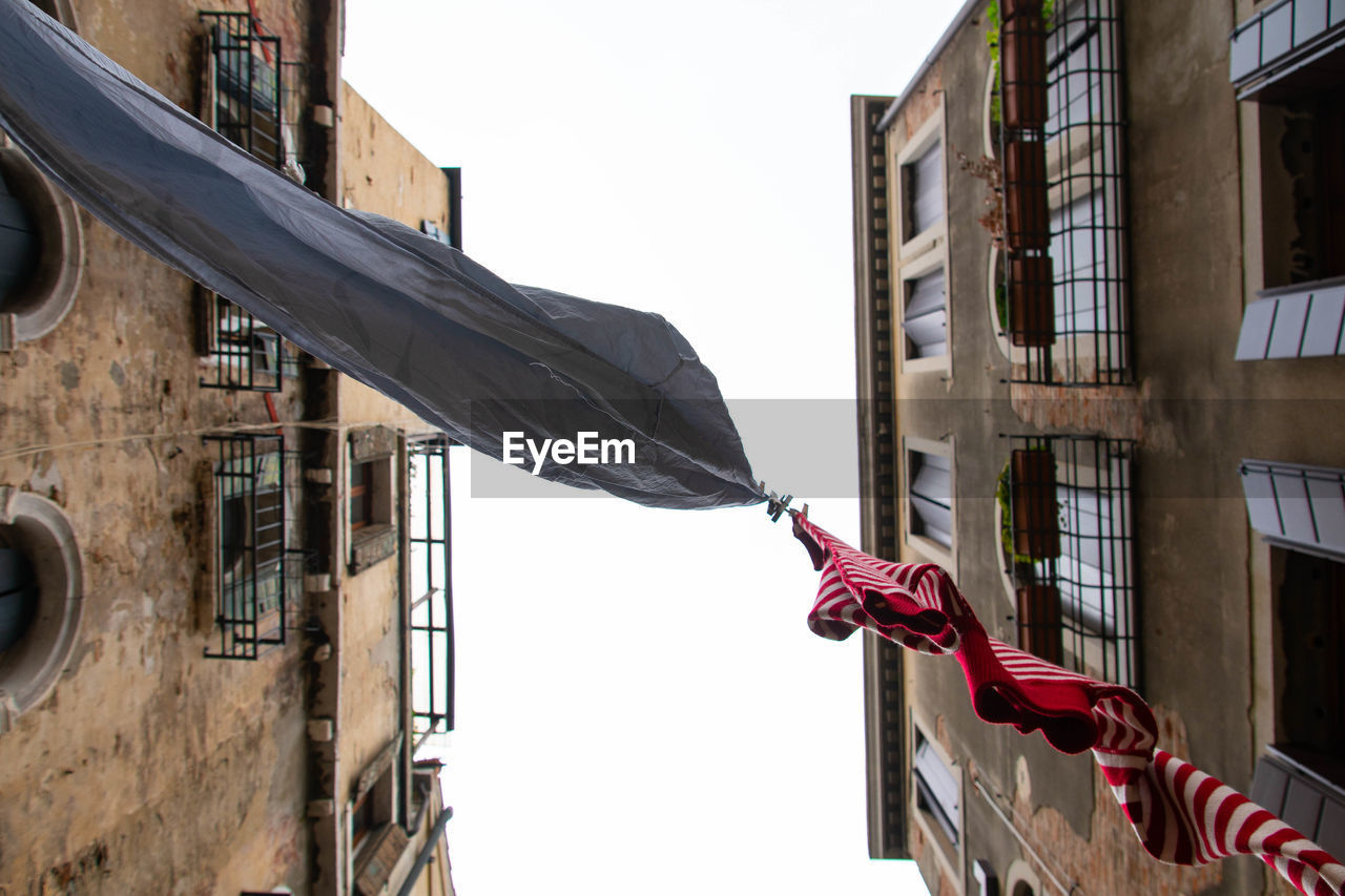 building exterior, built structure, architecture, building, low angle view, day, window, sky, hanging, flag, no people, residential district, drying, laundry, clothing, clear sky, clothesline, outdoors, nature, city, apartment