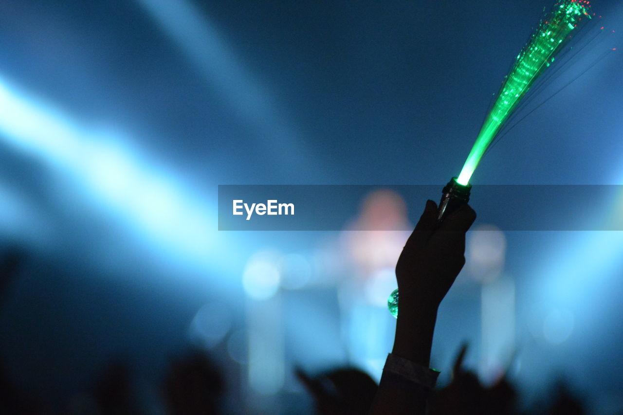 Close-up of hand holding illuminated lighting equipment at music concert