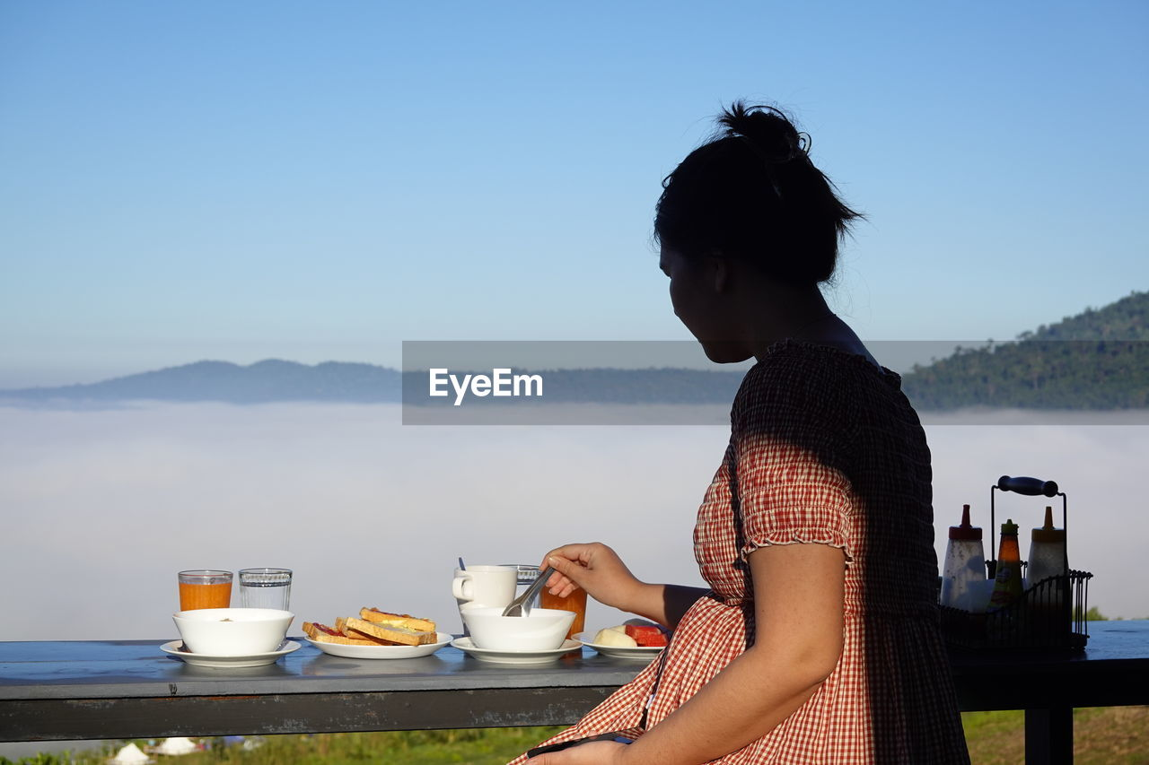 WOMAN SITTING ON COFFEE AGAINST SKY