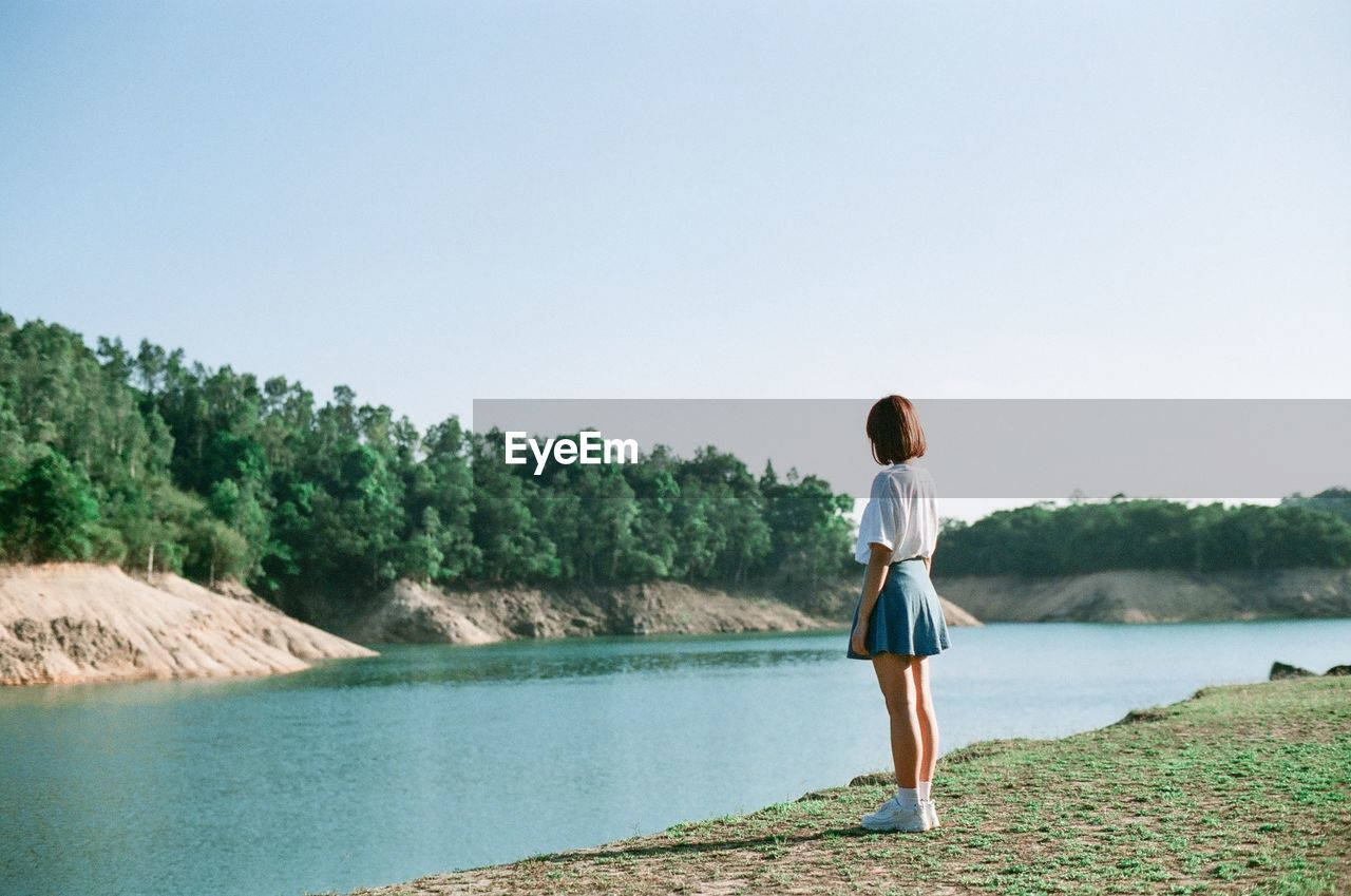 Young woman standing by river against clear sky