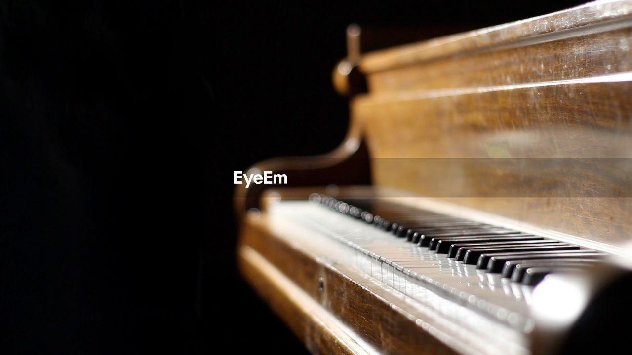 CLOSE-UP OF PIANO KEYS AT BLACK BACKGROUND