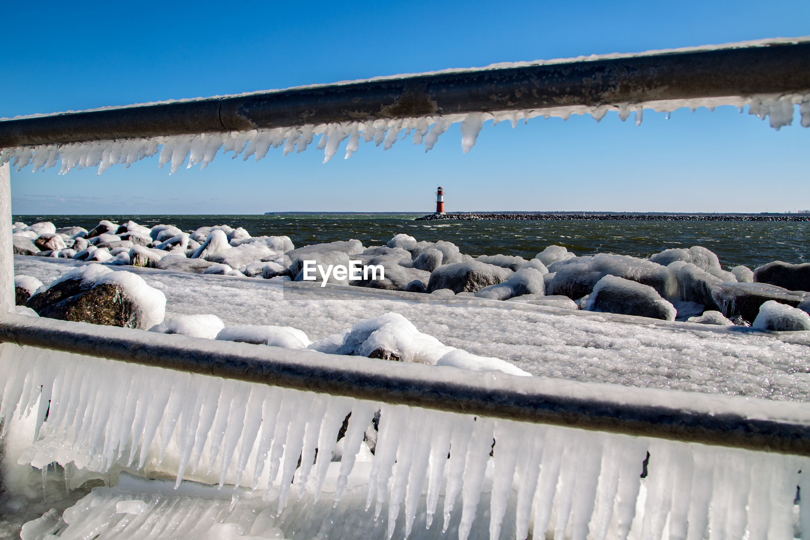 Close-up of icicles on railing by sea against clear blue sky