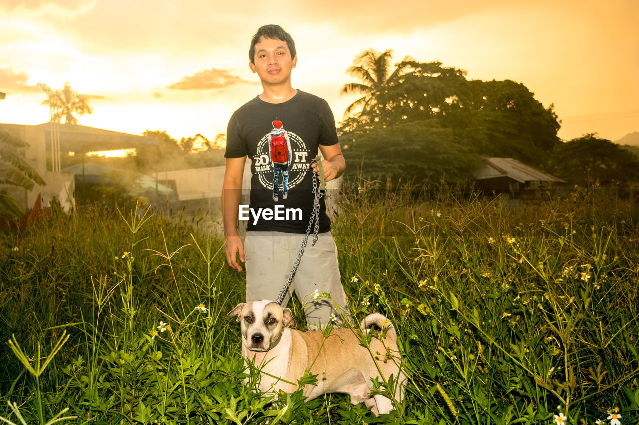dog, grass, pets, real people, one animal, mammal, outdoors, domestic animals, looking at camera, one person, leisure activity, sunset, nature, portrait, men, growth, building exterior, architecture, young adult, day, sky, people