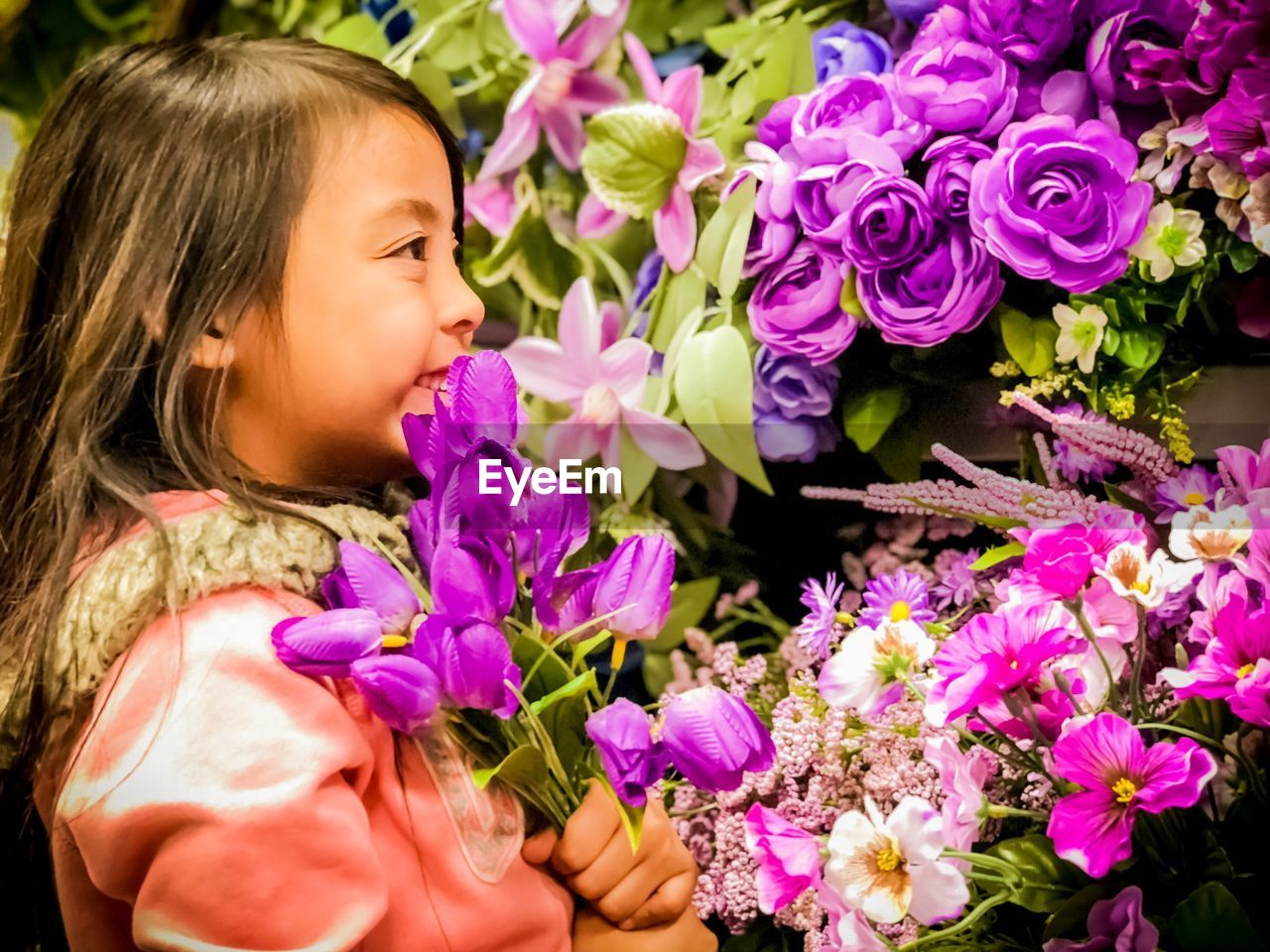 Close-Up Of Girl With Pink Flowers At Flower Shop
