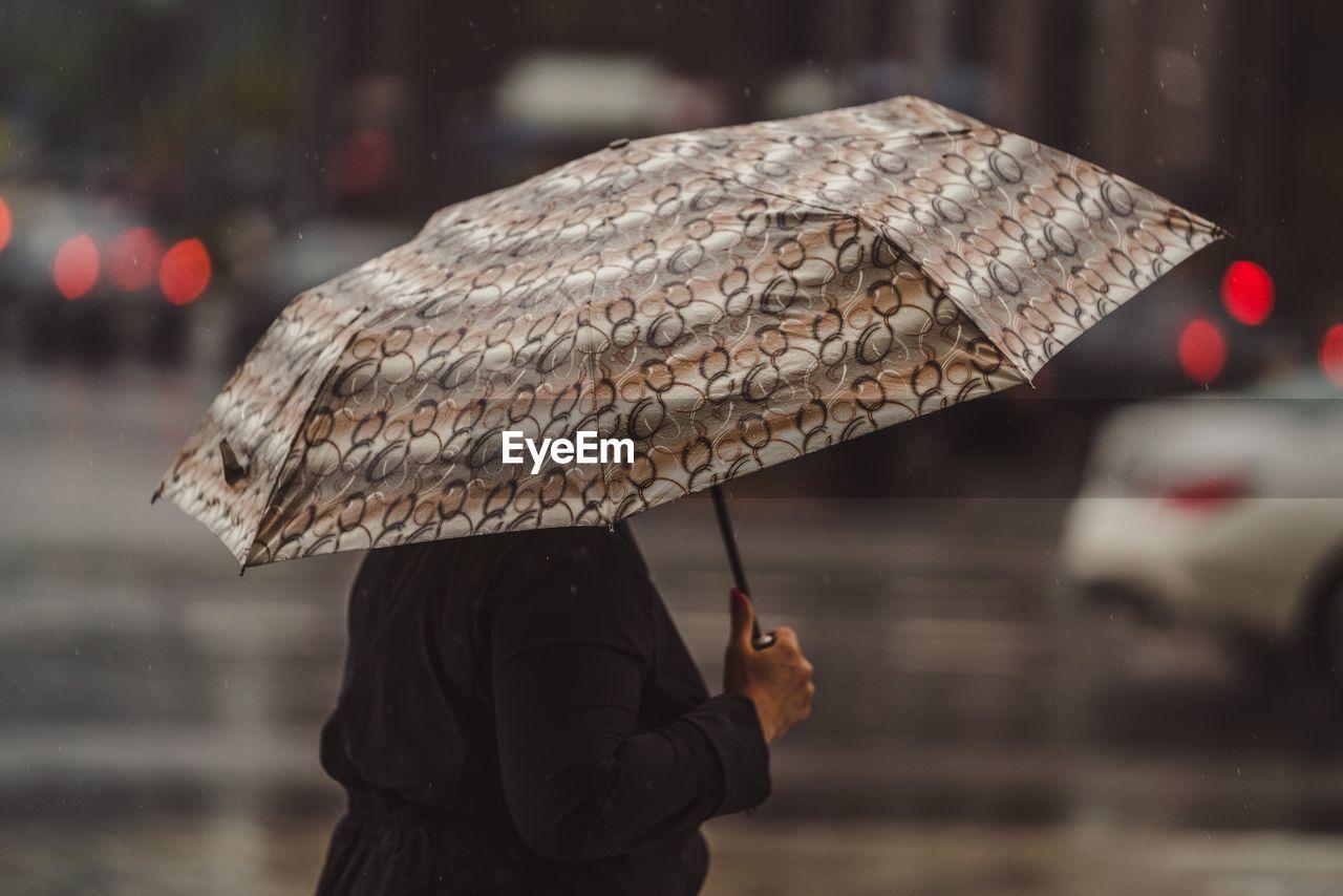 Woman With Umbrella Walking On Wet Street
