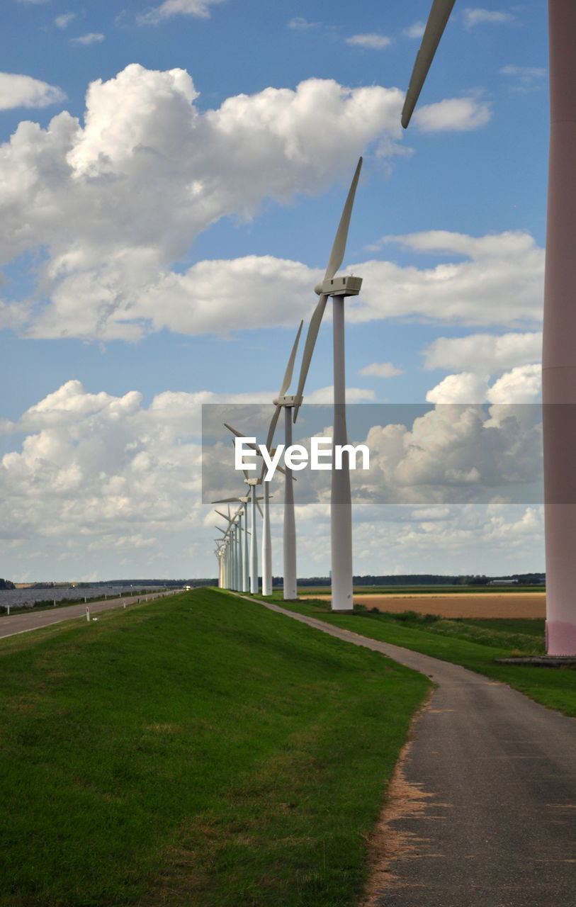 alternative energy, wind power, wind turbine, fuel and power generation, renewable energy, environmental conservation, sky, cloud - sky, windmill, day, field, no people, industrial windmill, grass, outdoors, rural scene, scenics, nature, landscape, road, beauty in nature