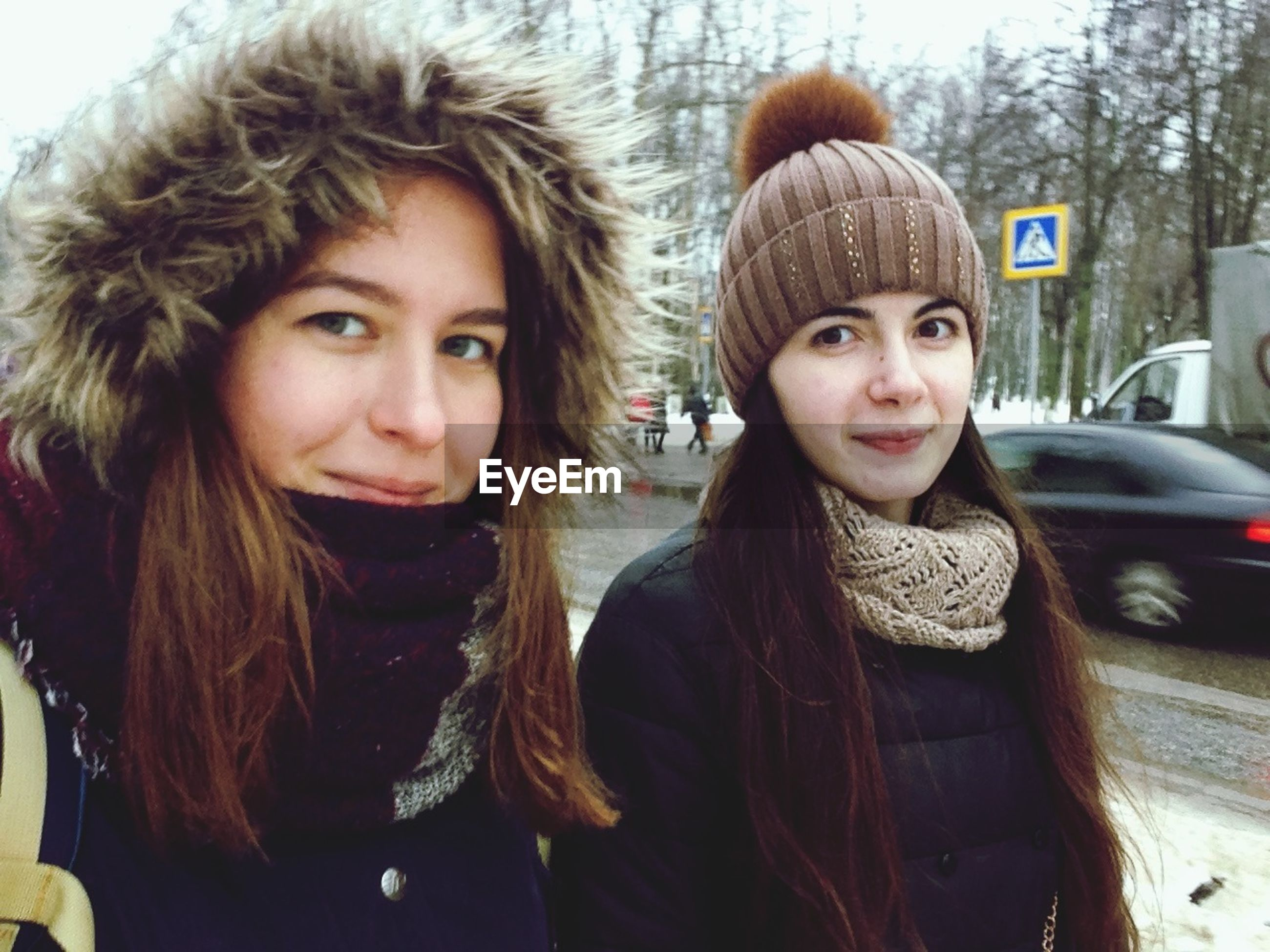 looking at camera, portrait, winter, warm clothing, two people, cold temperature, front view, real people, leisure activity, weather, smiling, headshot, lifestyles, young women, young adult, knit hat, fur hat, outdoors, snow, standing, women, togetherness, day, close-up, tree, architecture, people, adult