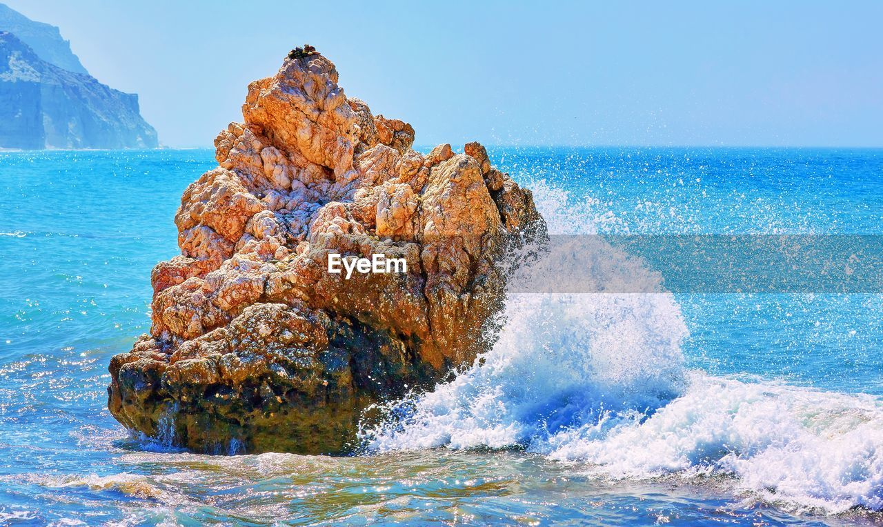 sea, water, horizon over water, beauty in nature, sky, wave, scenics - nature, rock, motion, horizon, nature, rock - object, blue, solid, land, beach, splashing, clear sky, day, no people, power in nature, breaking, hitting