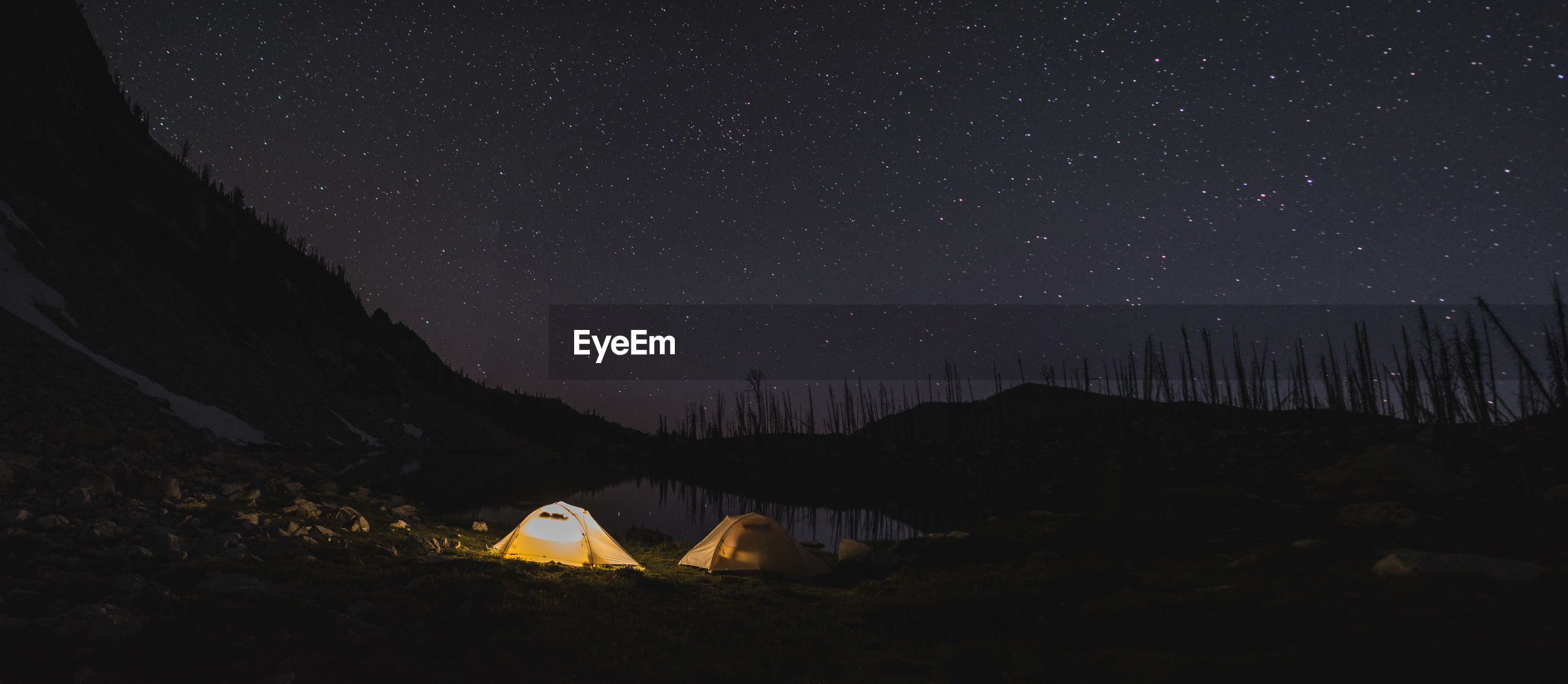 Illuminated tents on land against star field at night