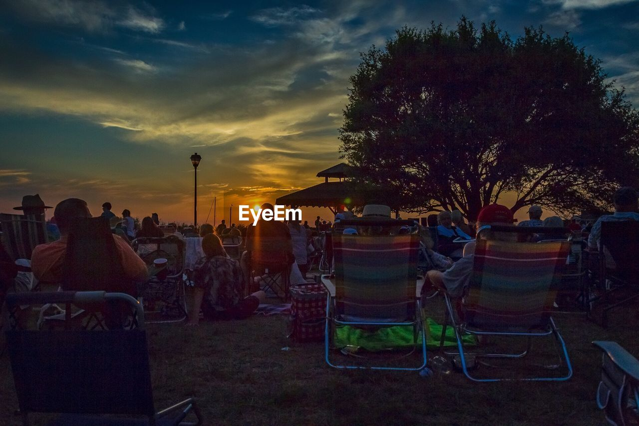 chair, sky, men, large group of people, outdoors, real people, cloud - sky, sunset, nature, tree, leisure activity, sitting, women, night, grass, people
