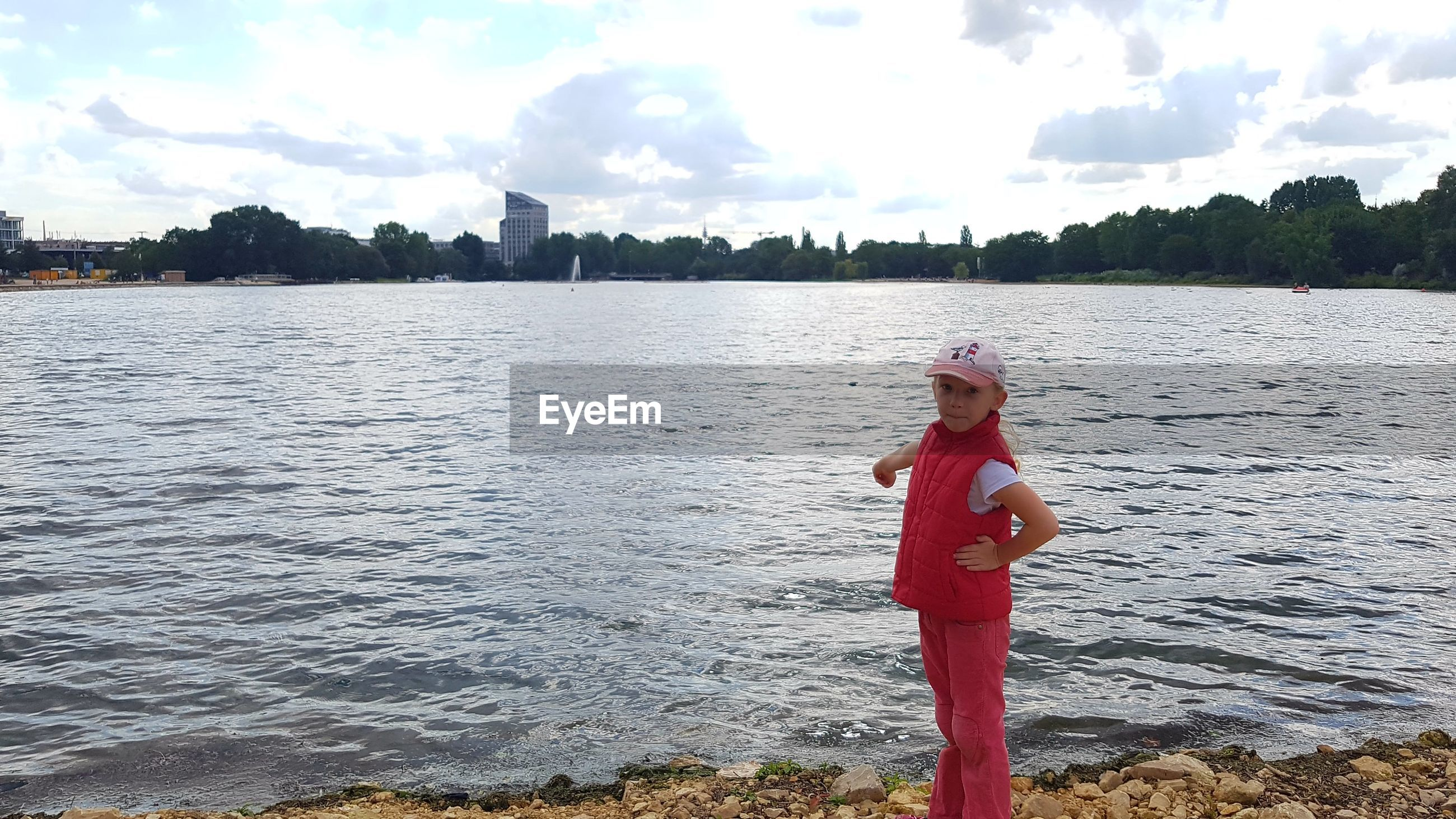Girl on riverbank against cloudy sky
