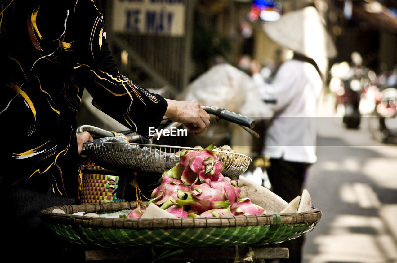 Midsection Of Person With Bicycle Selling Dragon Fruits