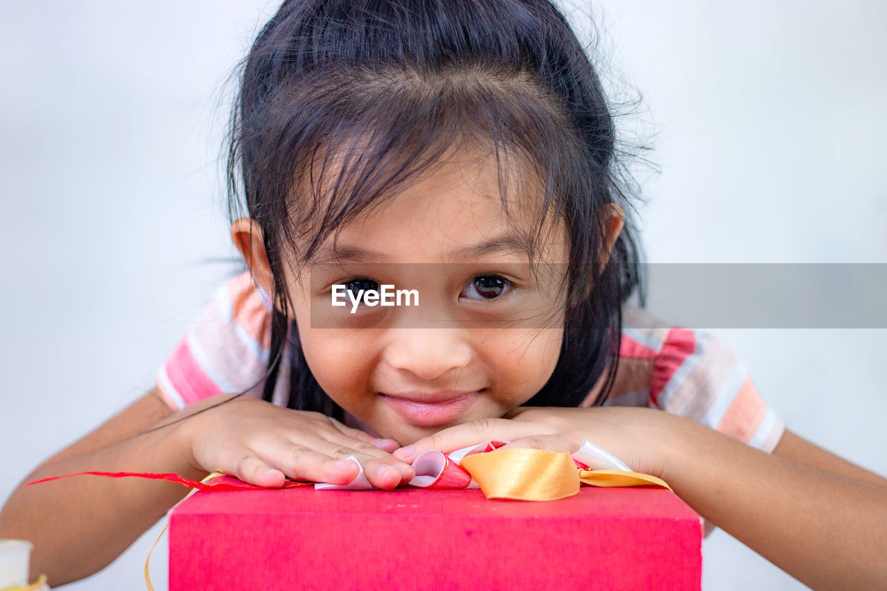 Portrait of cute girl leaning on gift box