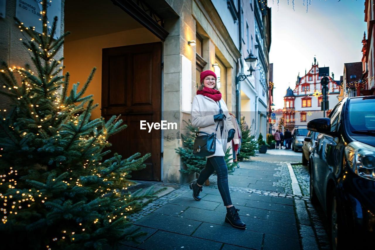 Full length of woman walking on footpath on street