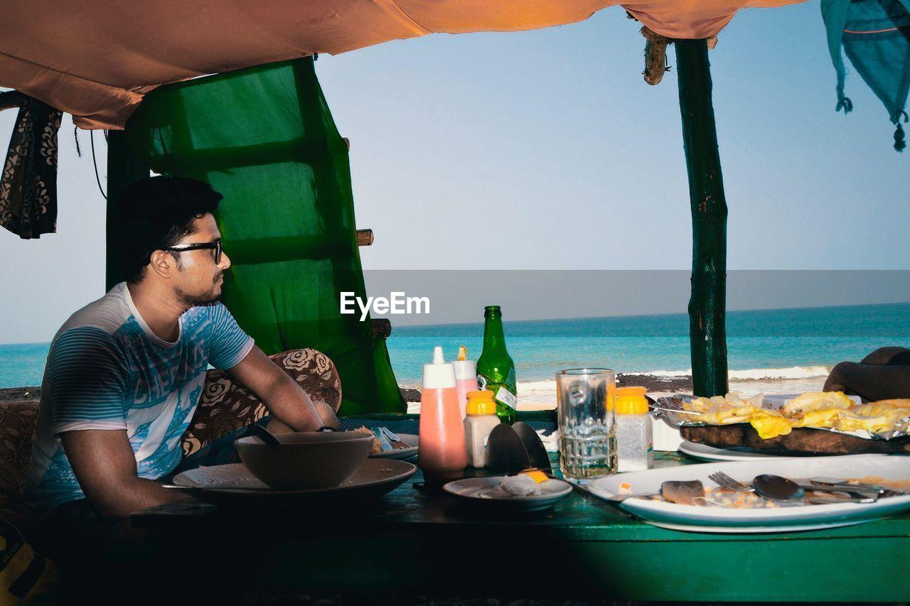 View Of Man Eating At Restaurant At Beach