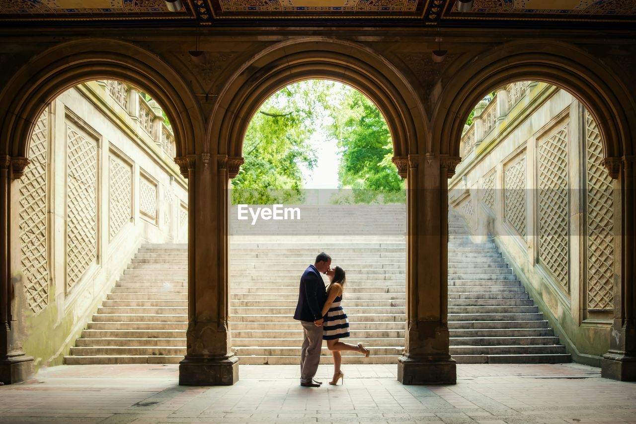 Full Length Of Couple Kissing In Historic Building
