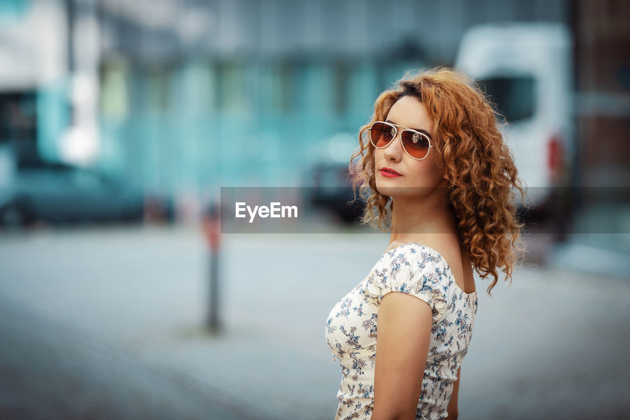 Young moroccan woman with curly hair, wearing sunglasses, turning to camera, in urban environment