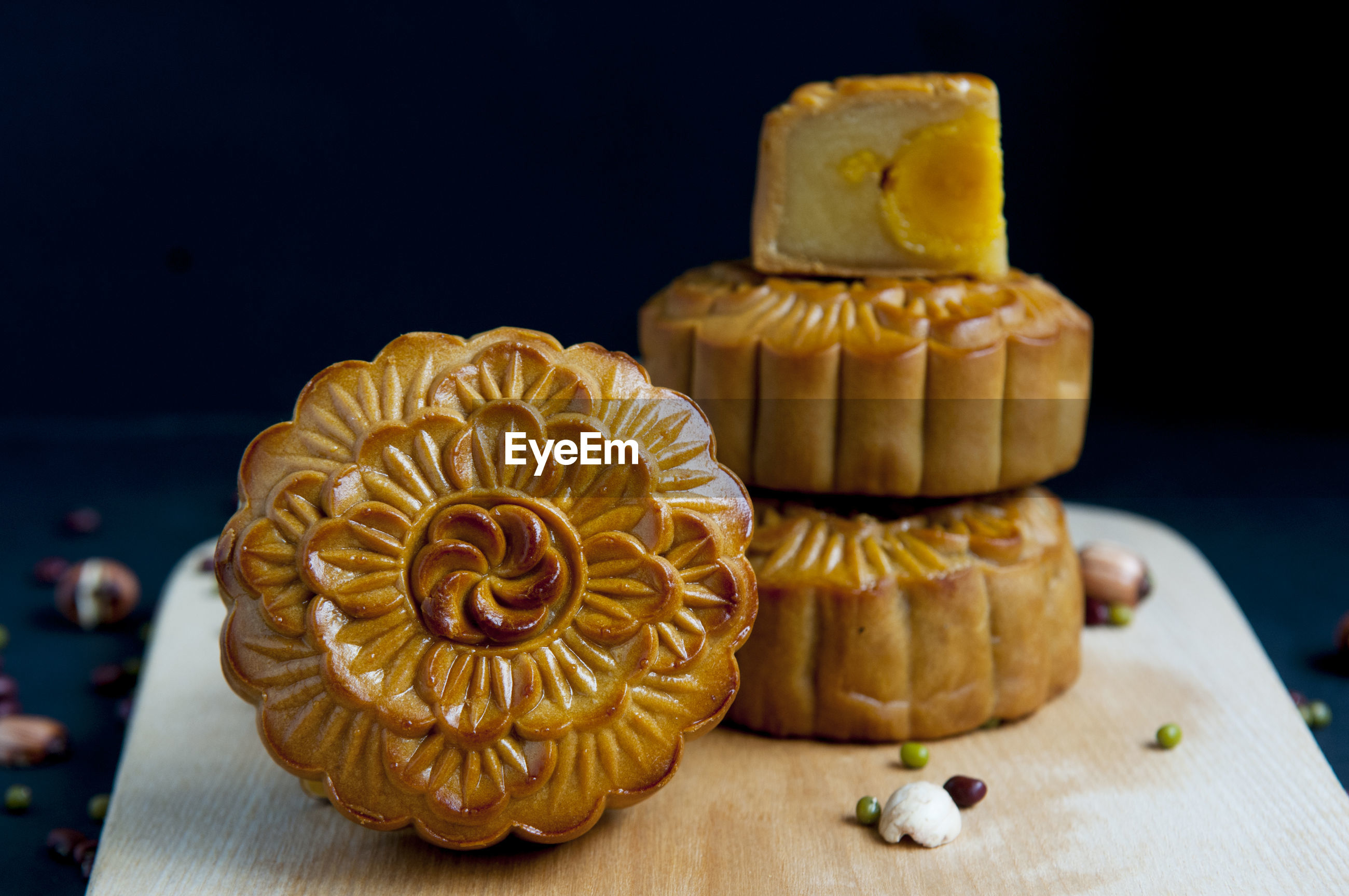 Close-up of moon cakes with seeds and serving board on table against black background