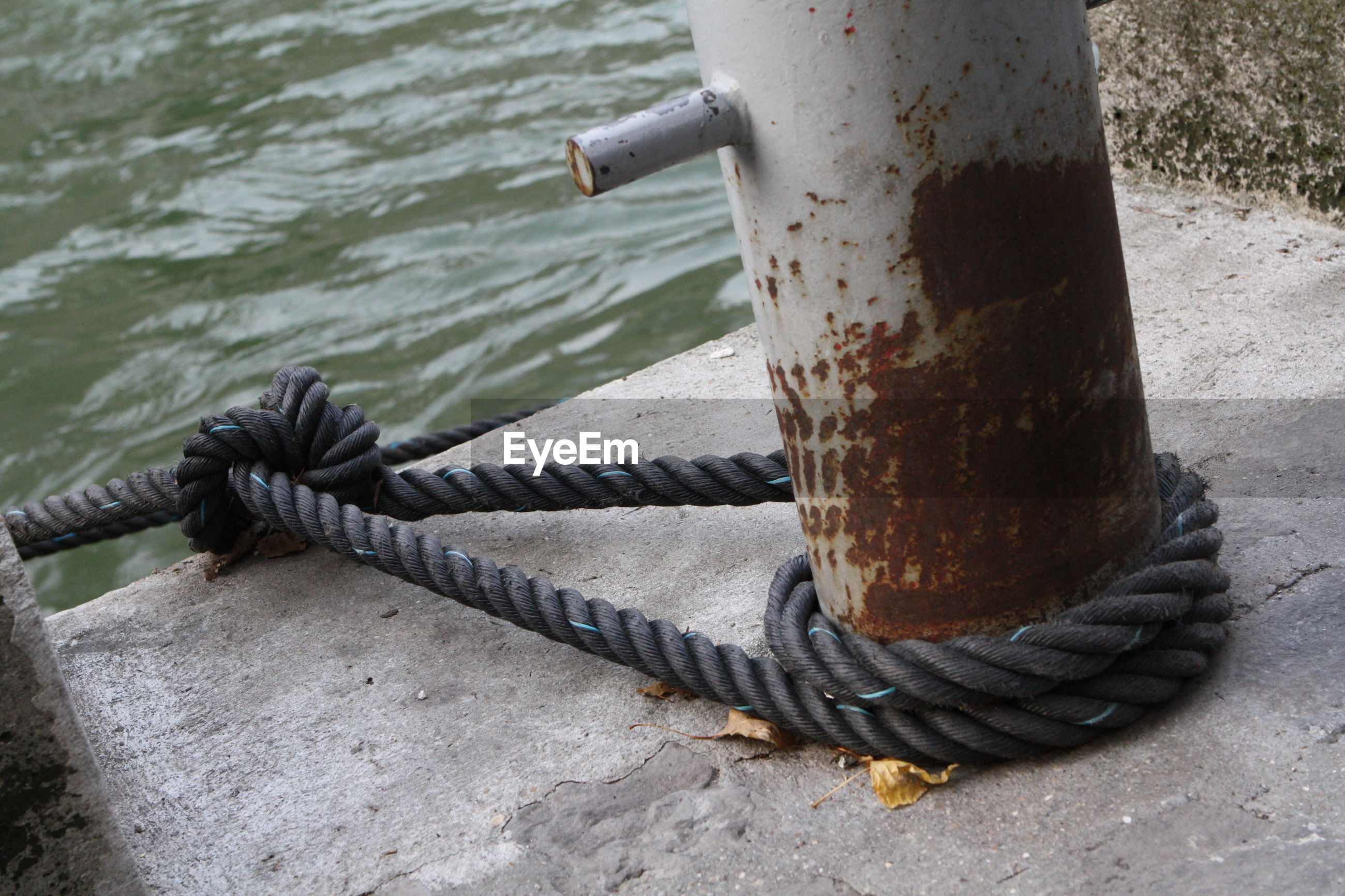 High angle view of rope tied up to rusty bollard