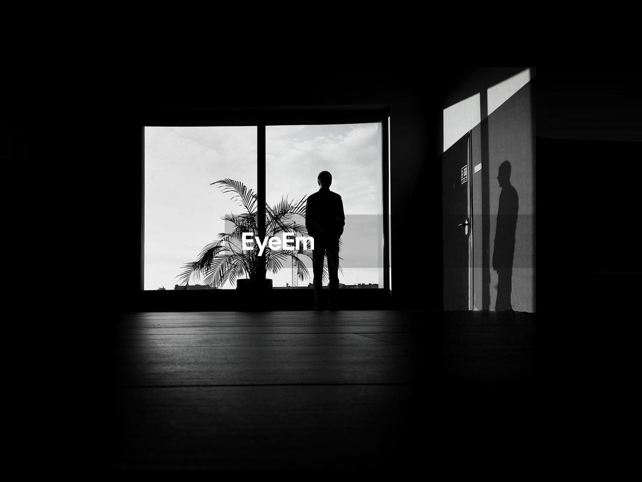 Silhouette man standing on floor against window