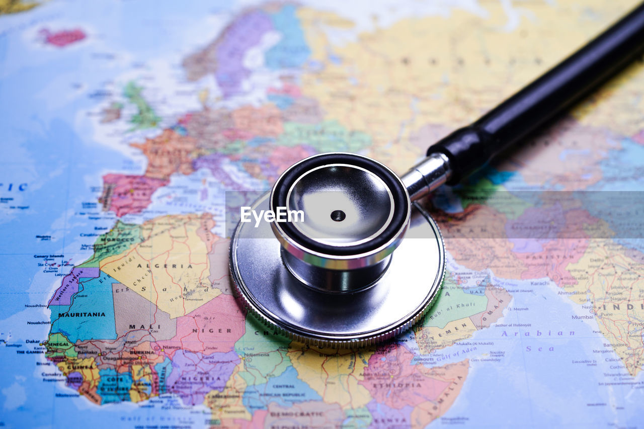 map, close-up, indoors, no people, direction, guidance, world map, high angle view, travel, still life, focus on foreground, medical supplies, selective focus, exploration, discovery, travel destinations, text, stethoscope, physical geography