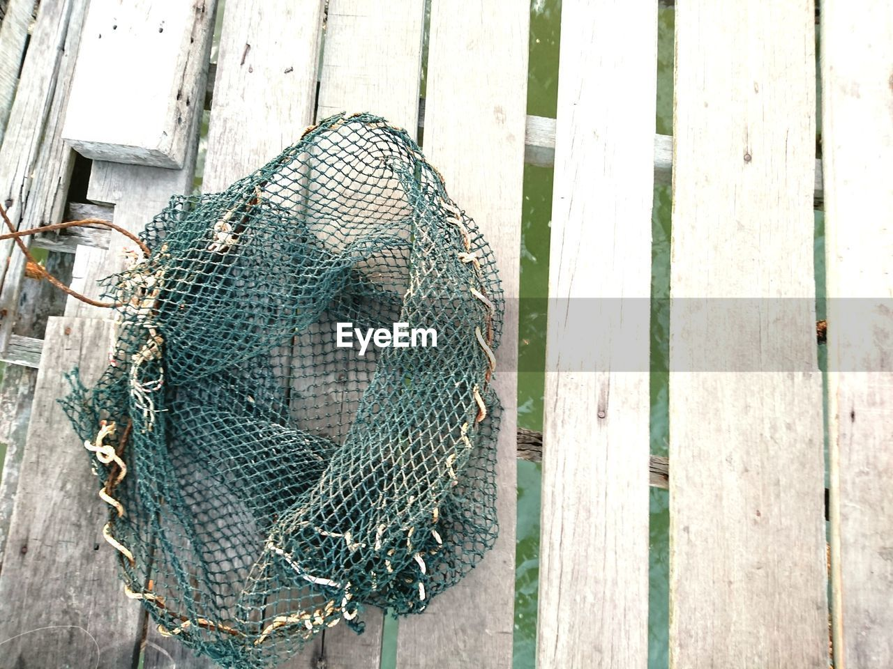 no people, day, fishing industry, fishing net, fishing, close-up, rope, wood - material, metal, commercial fishing net, outdoors, safety, security, wall - building feature, cage, high angle view, boundary, animal themes, pattern, animal
