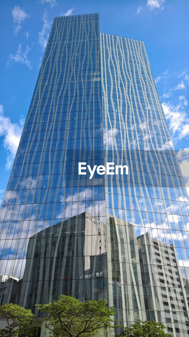 low angle view, architecture, sky, cloud - sky, day, built structure, no people, modern, building exterior, skyscraper, outdoors, growth, tall, city, tree
