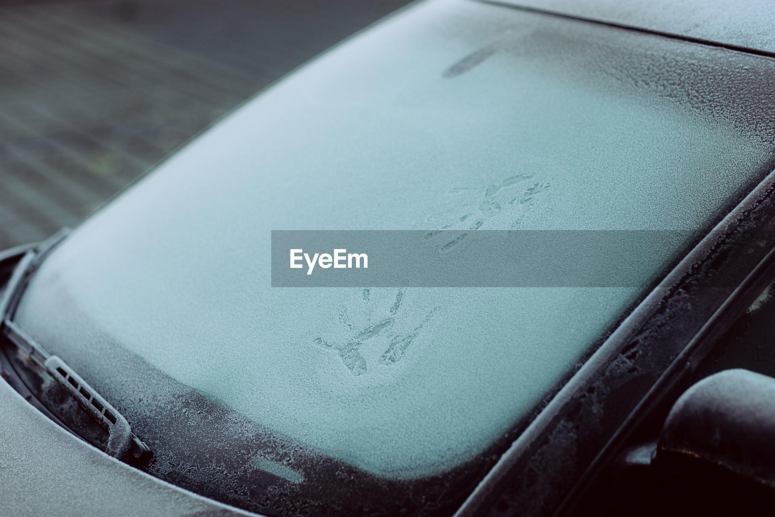 Close-up of handprints on frozen car windshield