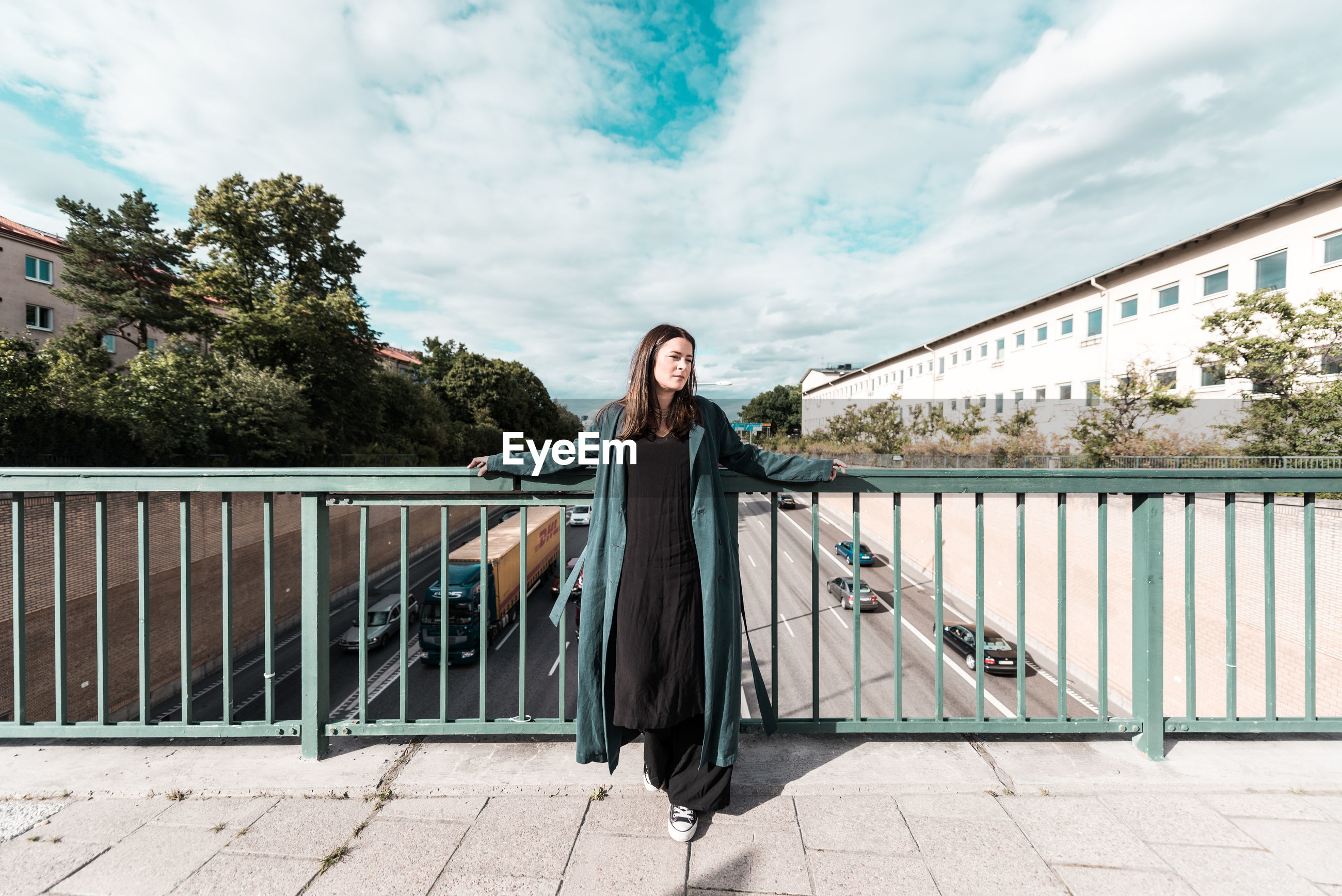 Mid adult woman standing by railing on footbridge against cloudy sky