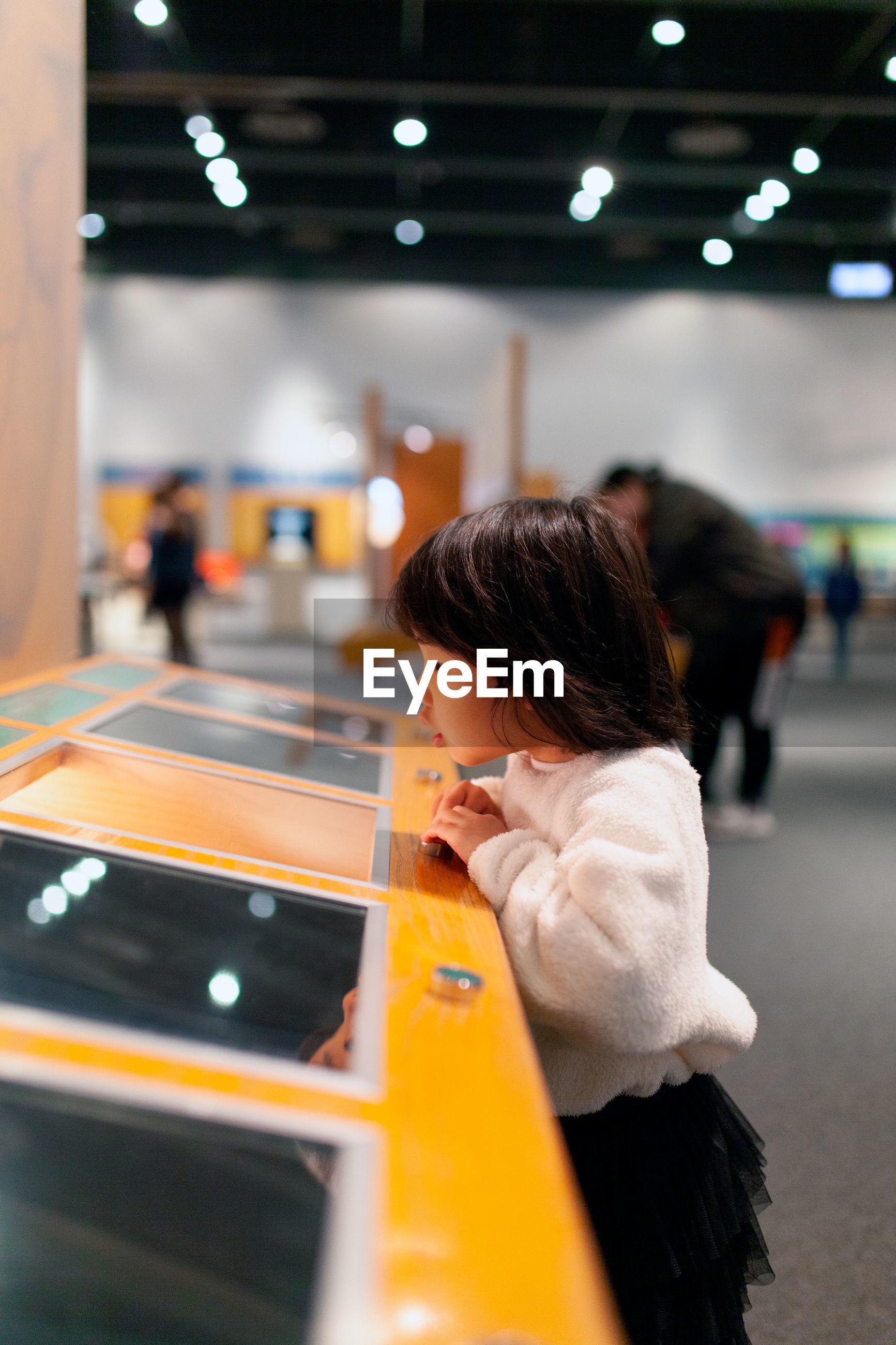 Cute girl looking at illuminated game