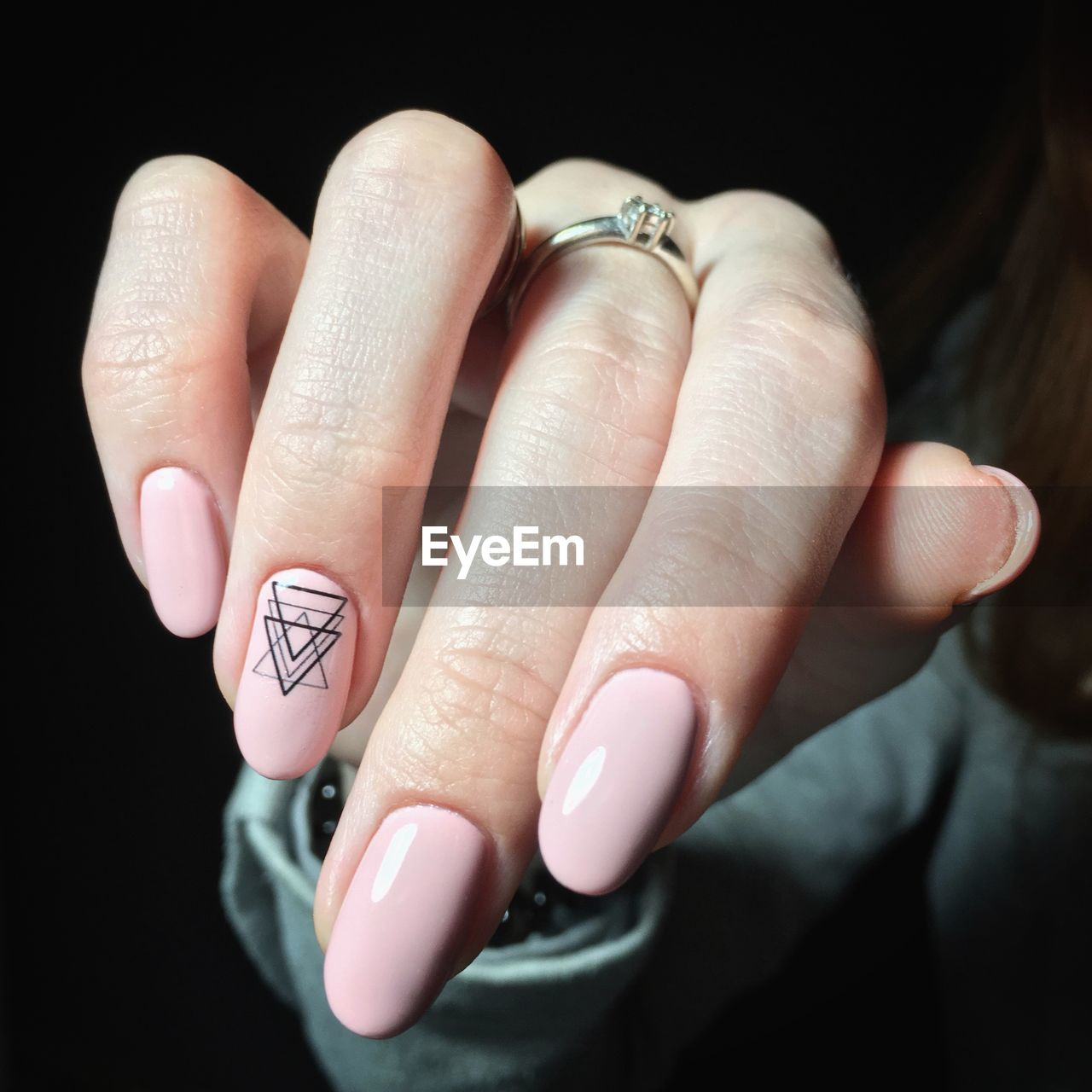 human hand, hand, human body part, finger, body part, human finger, one person, jewelry, ring, close-up, indoors, women, adult, real people, nail, nail polish, showing, lifestyles, focus on foreground, black background, personal accessory, nail art