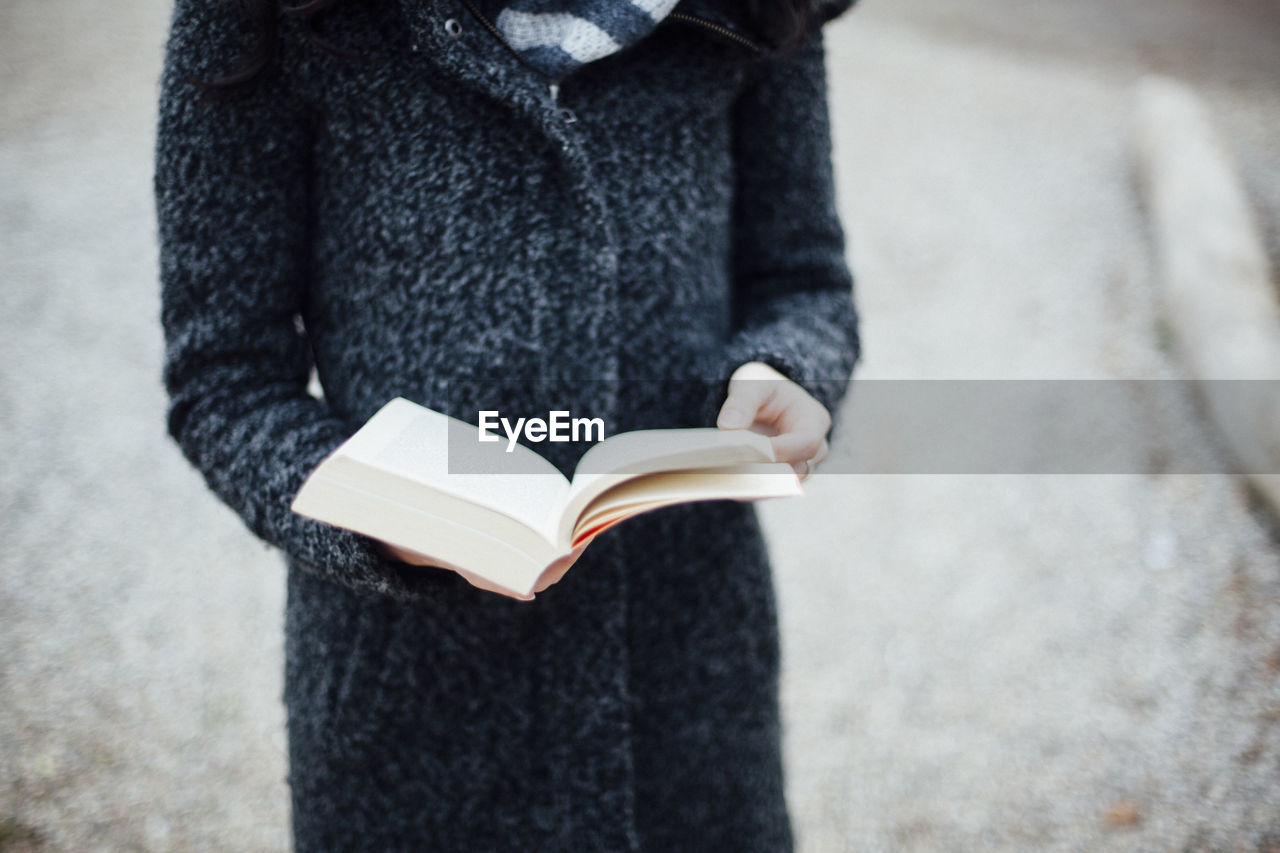 Midsection Of Woman Holding Book On Field