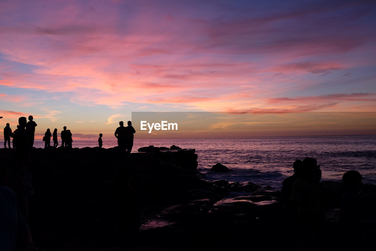 sky, sunset, silhouette, sea, group of people, real people, beauty in nature, orange color, scenics - nature, rock, water, beach, solid, rock - object, land, lifestyles, men, leisure activity, nature, horizon over water, outdoors