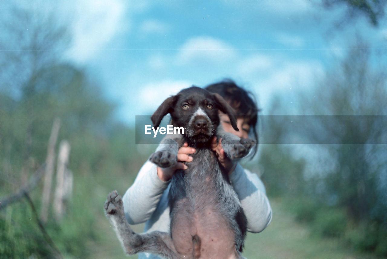 Girl holding dog on field