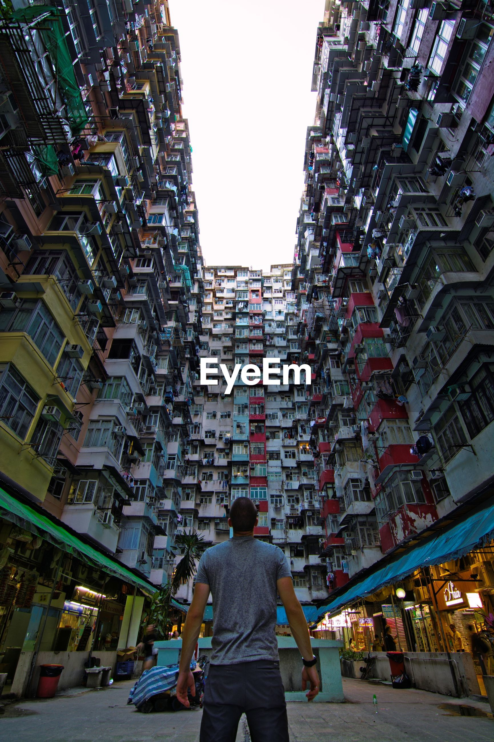 FULL LENGTH REAR VIEW OF MAN WALKING ON STREET AGAINST BUILDINGS