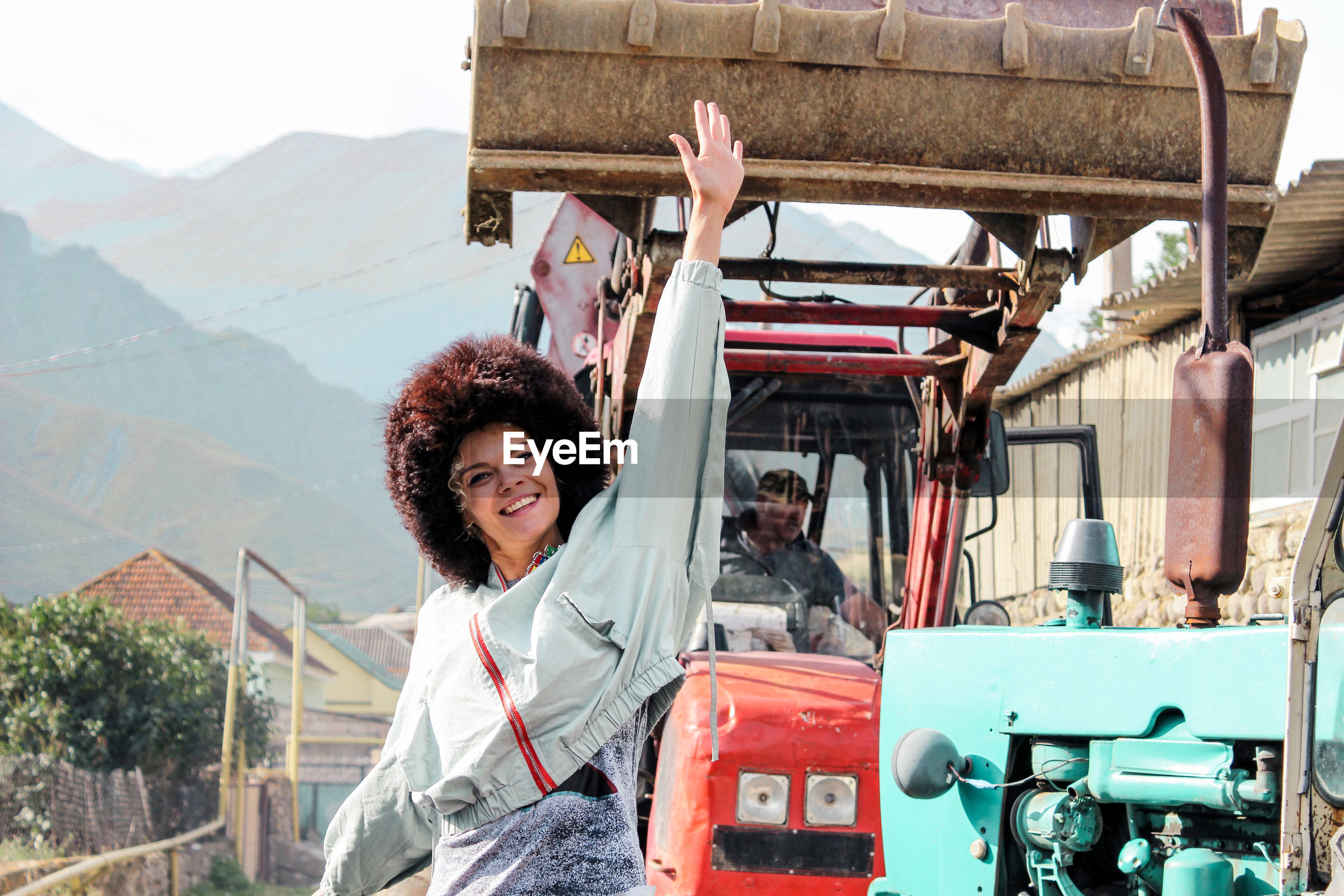 Portrait of smiling young woman with arm raised standing against earth mover