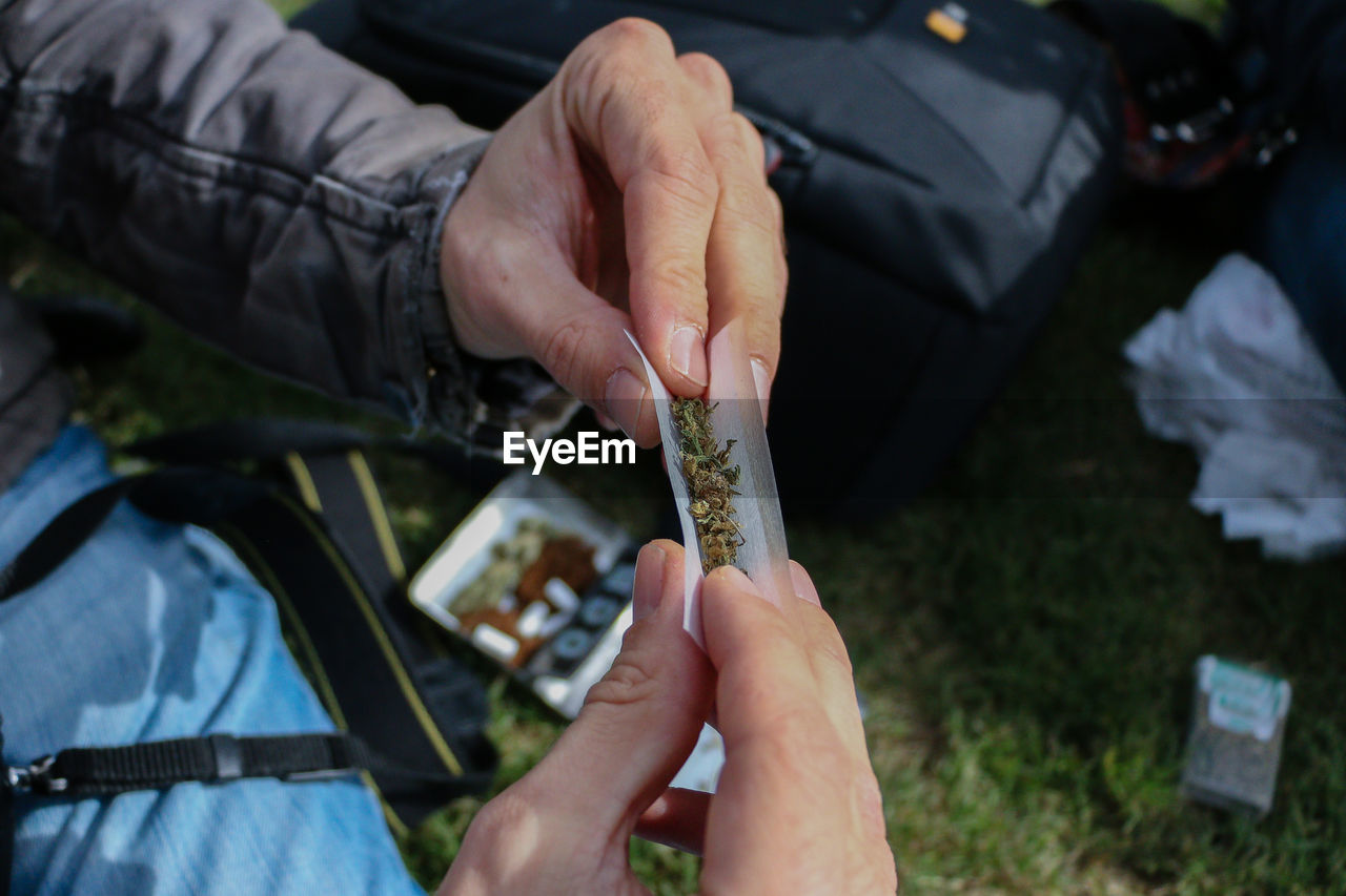 Cropped hands of man making marijuana joint on grass