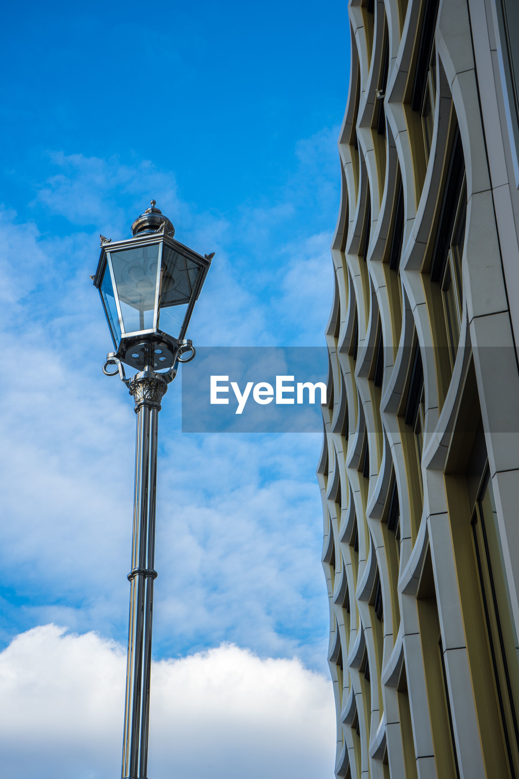 low angle view, sky, cloud - sky, architecture, street light, street, lighting equipment, built structure, building exterior, no people, nature, day, city, blue, building, outdoors, tall - high, office building exterior, metal, glass - material, light, skyscraper, apartment