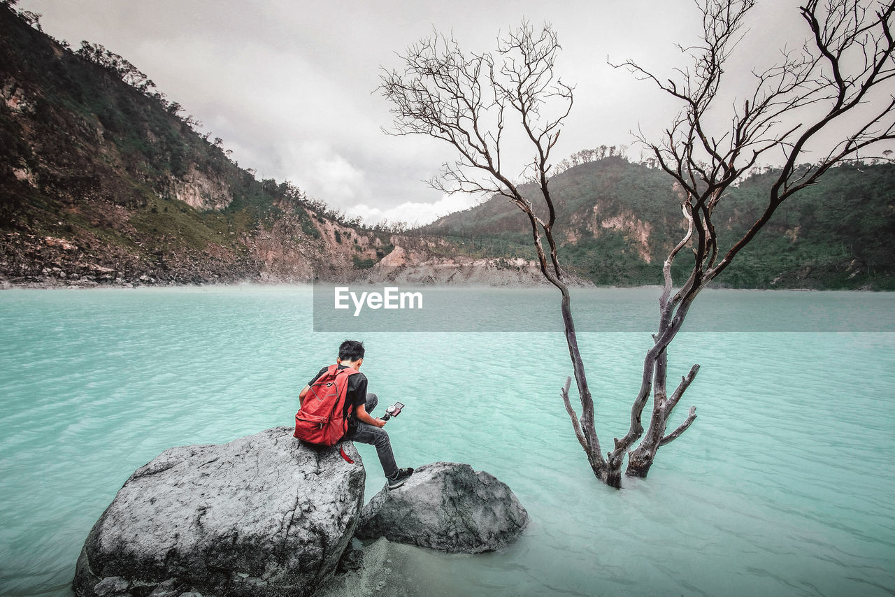Rear View Of Backpacker Sitting On Rock By Lake Against Sky