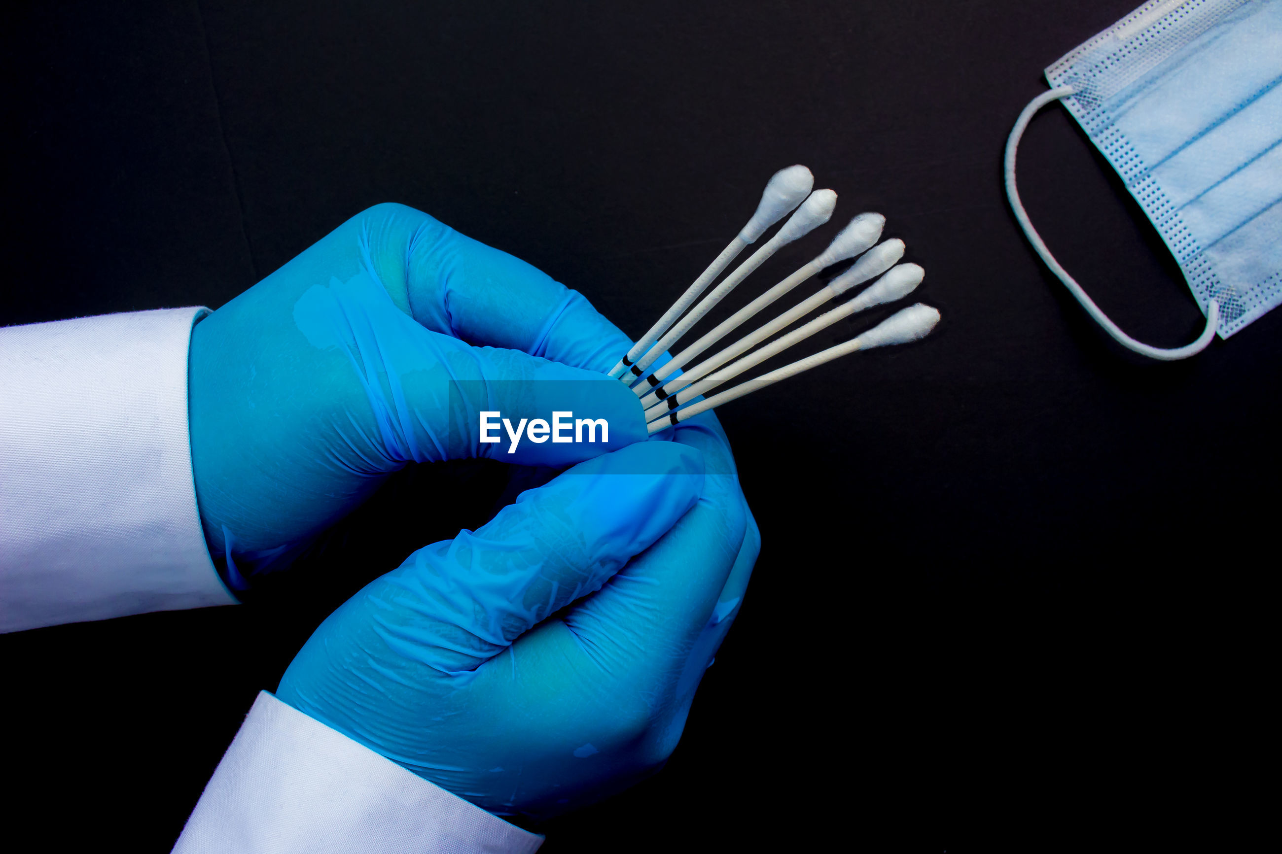 Cropped hands of surgeon holding cotton swabs against black background