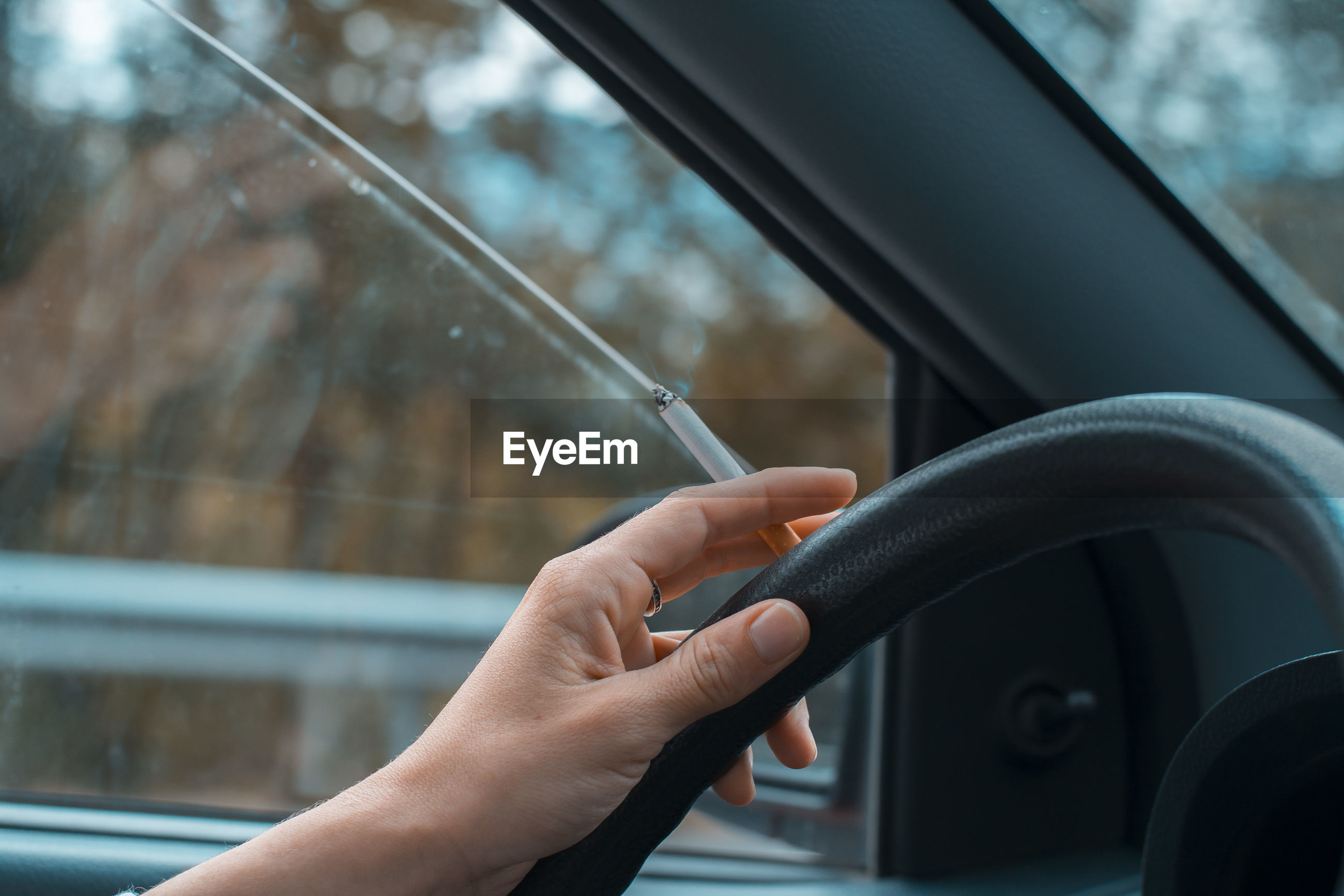 Cropped hand of person holding cigarette while driving car