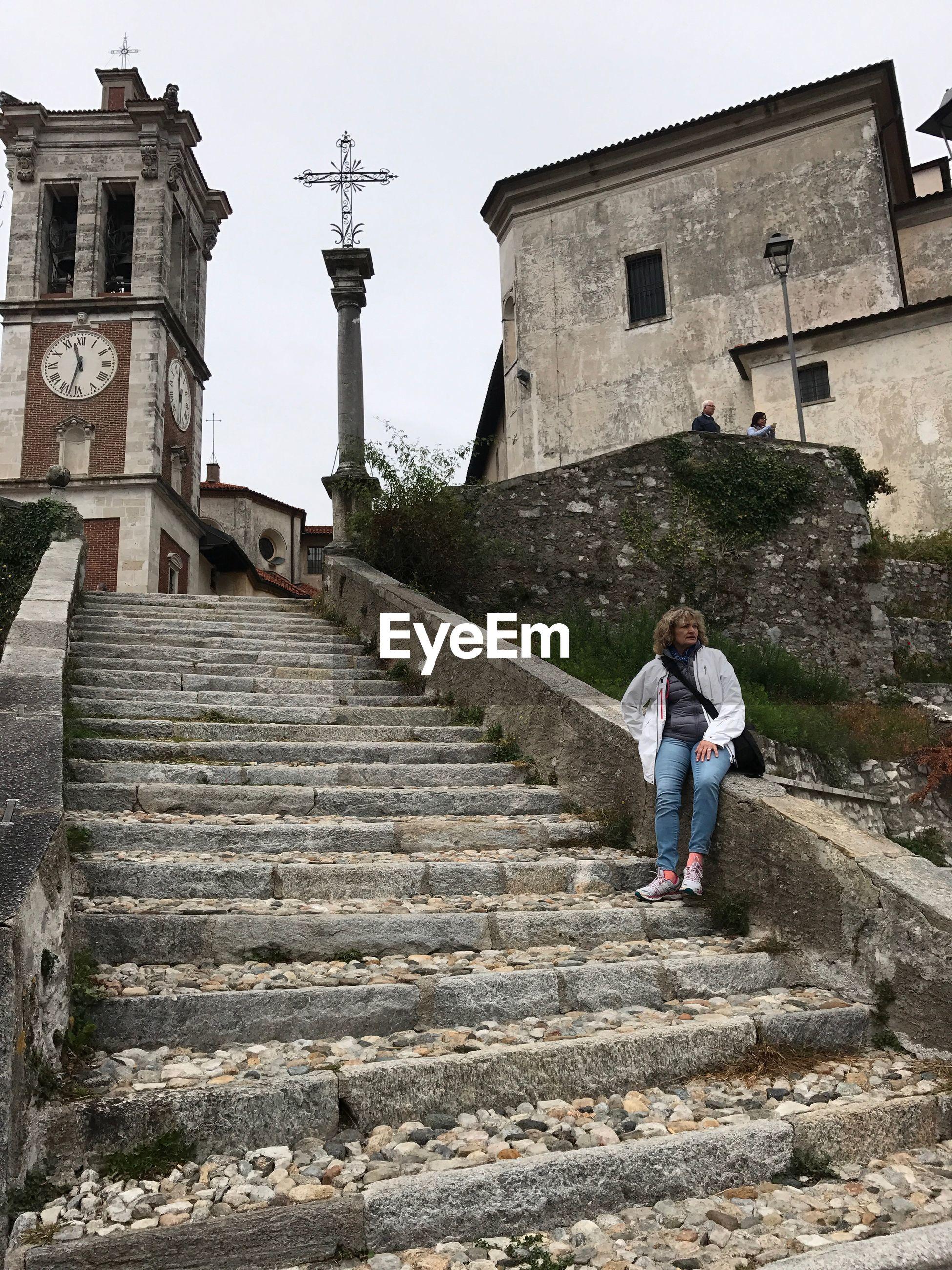 Woman sitting on steps against church