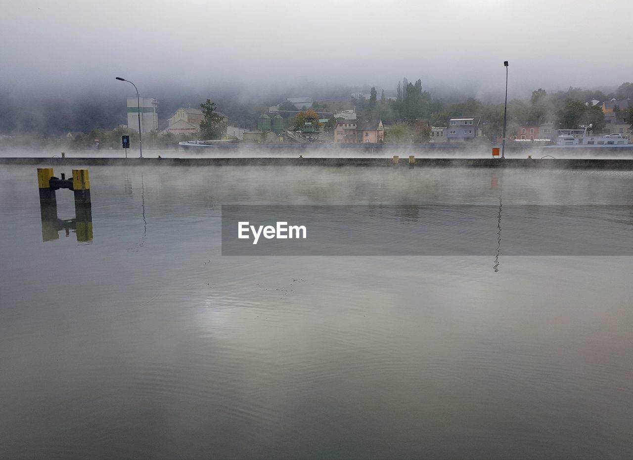 water, reflection, fog, waterfront, sky, nature, architecture, no people, building exterior, built structure, lake, day, outdoors, cold temperature, winter, beauty in nature, city, tranquility, rain