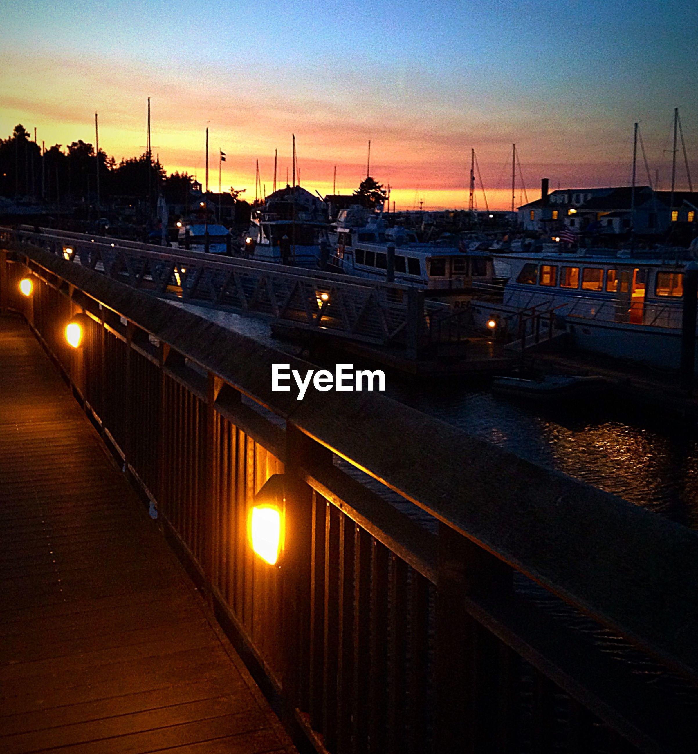 Illuminated street light on railing by river at sunset