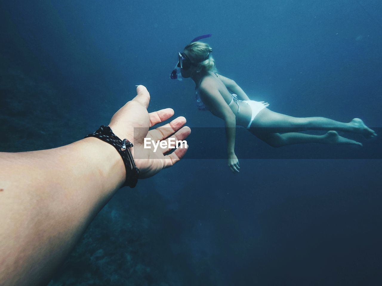 Cropped hand of man gesturing at female friend snorkeling in sea