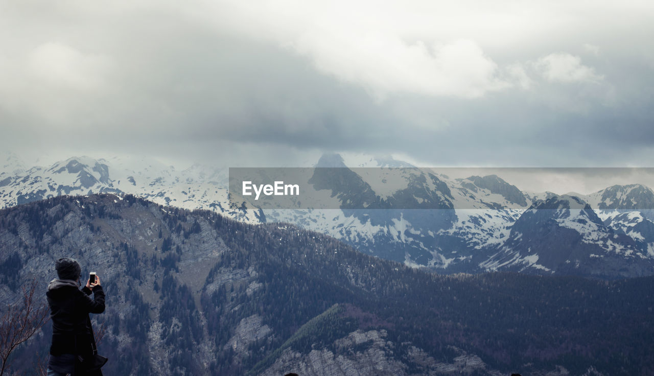 Rear View Of Photographing Snow Covered Mountains Against Cloudy Sky